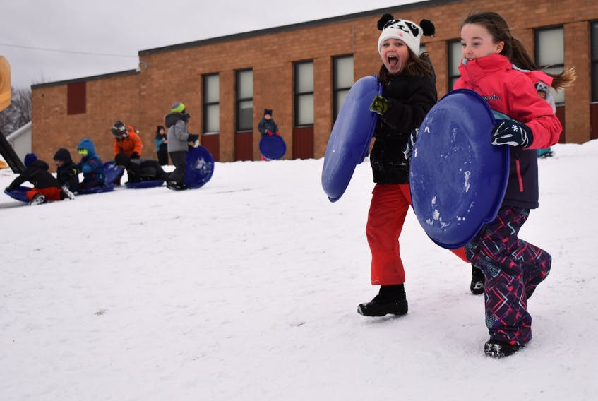 Stori Corbett, 8, left, and Lydia Jarrett, 8, take a running start before jumping on their sleds at Robin Foote Elementary on Thursday. Last year, the school bought sleds for students to use during recess and lunch breaks. The students love it and so do the teachers, who say students pay more attention in class after spending their break sledding.