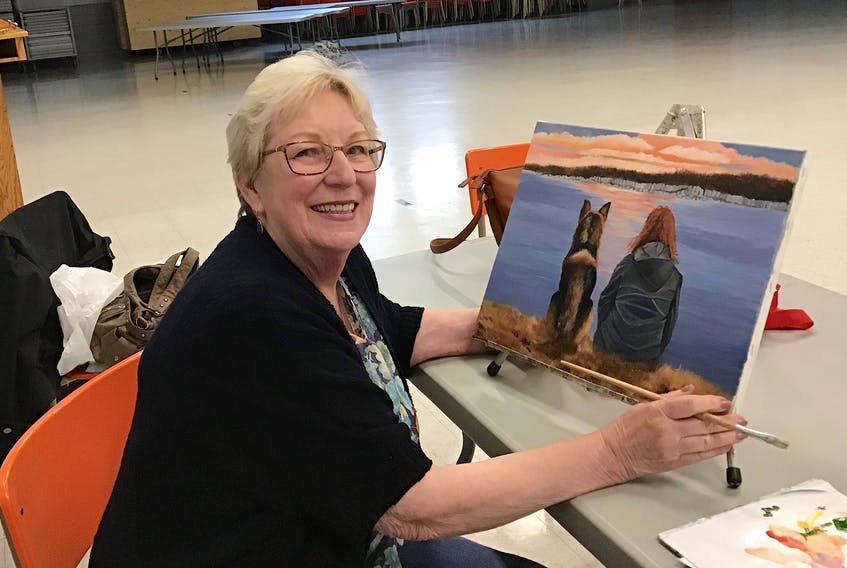 """Cecilia McIntosh holds her painting """"Big Harbour,"""" one of the works of art on exhibit during the annual Glace Bay Art Group show being held at the Glace Bay Fire Hall. The show runs June 12 and June 13 from 1 p.m. – 8 p.m."""