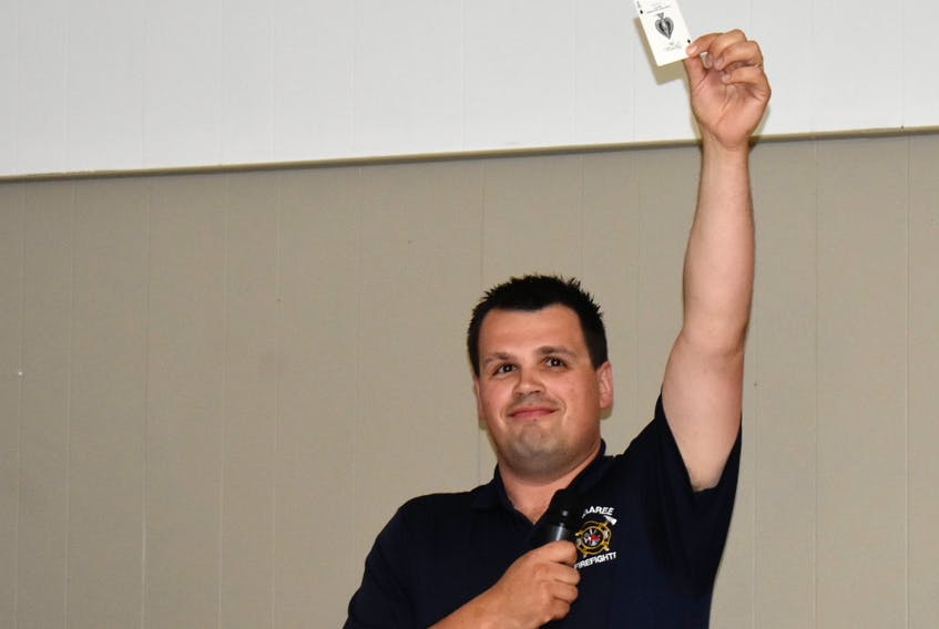 Margaree firefighter Jason McDaniel holds up the ace of spades after picking for winners Barb Reddick and Tyrone MacInnis, who weren't in attendance. The pair, who couldn't be immediately reached by phone, will split the $1.2-million prize.