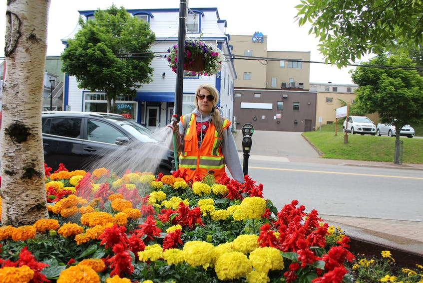 It takes a lot of effort to keep the flowers in front of the Cape Breton Regional Municipality's civic centre  bright and colourful throughout the summer. Sarah Jean Lohnes is among those who perform that job. The CBRM summer employee is shown watering the flowers early on Thursday morning.