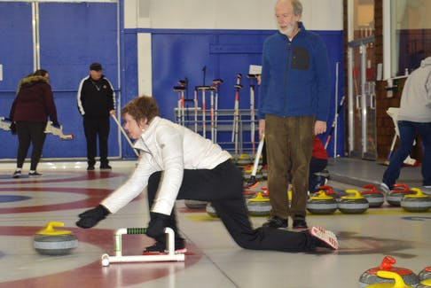 Cynthia Boutilier is taught how to curl by Ron Labelle during the Taste of Winter: Learn to Curl event at the Sydney Curling Club on Saturday.