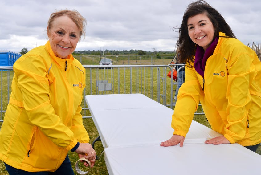 Volunteers Linda MacMillan, left, and Tanya Hardy, both members of the Rotary Club of North Sydney, were busy wrapping tables on the Ribfest Grounds at Sydney's Open Hearth Park on Thursday, in preparation for this weekend's Rotary Ribfest event opening today (Friday).