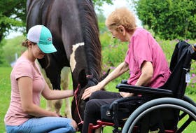 Caitlin Carter, left, holds her horse Breagha while R.C. MacGillivray Guest Home resident Francis Waters pets its nose. Facility recreation director Kim Hooper said Waters rarely takes part in activities but was so excited to see the horses she decided to come down from a nap.