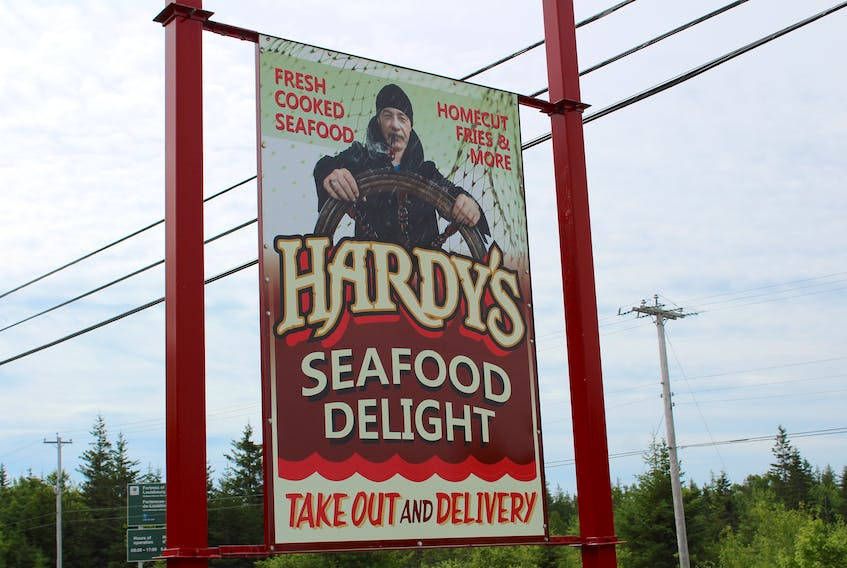 The sign for Hardy's Seafood Delight on Mira Road a few days before it was taken down. Owner Kevin Hardy, pictured in the sign, says the Cape Breton Regional Municipality isn't doing enough to help small businesses stay afloat.