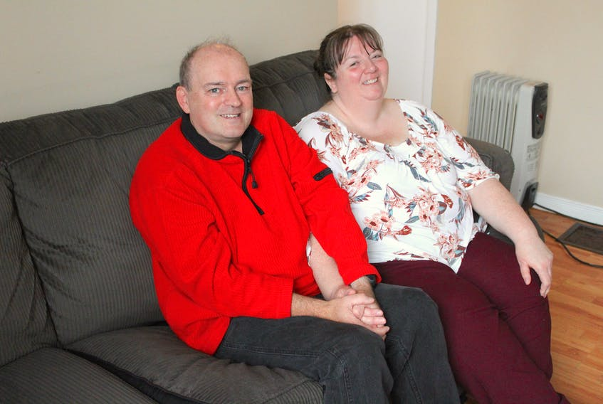 Gordon MacNeil (left) and his wife Debbie sit on the sofa in the living room of their Glace Bay home on Sept. 11. Dedicated to helping their community, Gordon got Debbie involved in the Alzheimer's Café's he co-ordinates annually at the Mayflower Mall shortly after they met. The self-taught musician wanted to help educate people about Alzheimer's disease and dementia after he started volunteering his time playing live and hosting karaoke at long-term-care facilities in the Cape Breton Regional Municipality in the 1990s.