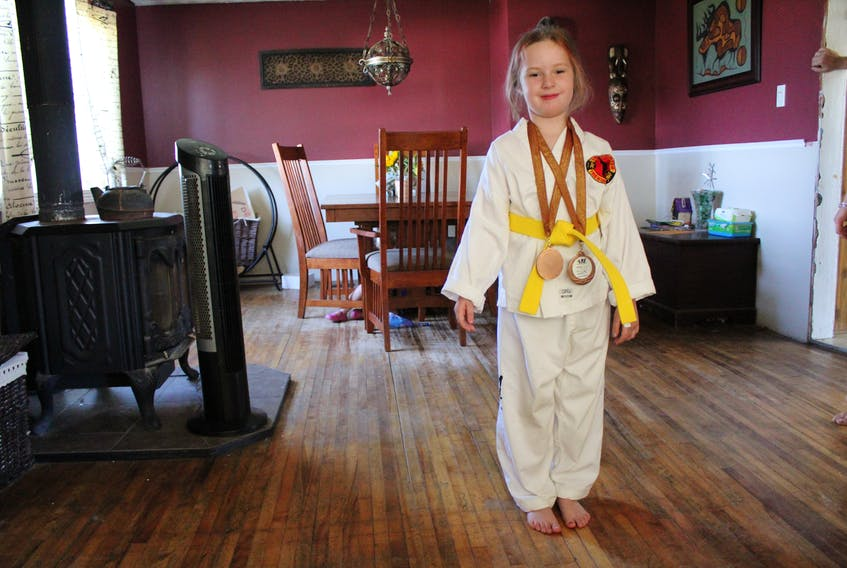 Neveah Beevor, seven, proudly wears her Integrity Martial Arts taekwondo uniform, yellow belt and two bronze medals she won at her first competition. Since starting at Integrity Martial Arts in December, the Greenfield Elementary student has gained confidence, happiness and movement in her right hand, which was partially paralysed because of a stroke she had at six-months-old.