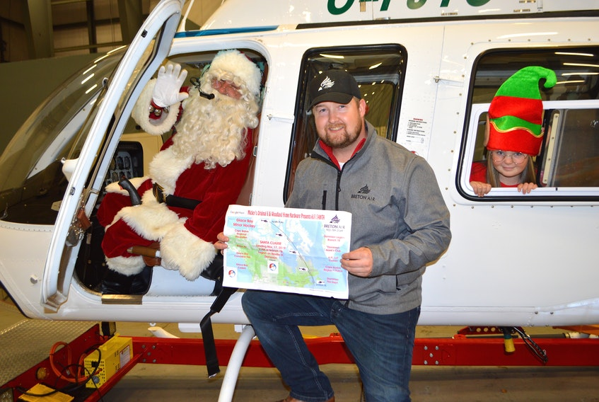 Santa Claus and his elf Jordyn Jingles wave from a Breton Air helicopter while going over plans with Parker Horton, CEO of Breton Air in Reserve Mines, to bring him, Mrs. Claus and Jordyn Jingles to Dominion by helicopter on Sunday. The helicopter will land at the Royal Canadian Legion branch 78 at 2 p.m.