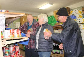 From the left, Carmen Hood, Sally Ryan and Calvin Gillard stock the shelves at the North Sydney Community Food Bank. These days officials at the food bank are preparing for Christmas orders and activities.