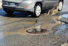 A car splashes through a pothole on Kings Road, approaching the lights at Kenwood Drive going into Sydney, on March 13. The potholes have been refilled multiple times since November by the Department of Transportation and Infrastructure Renewal. Coincidently, the most recent refilling was on the night of March 13.