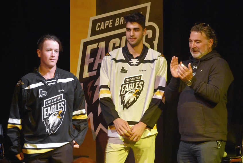 """Cape Breton's Quebec Major Junior Hockey League team announced a rebrand on Wednesday that featured a new logo. The team has also dropped the word """"screaming"""" from its name and will now be known as the Cape Breton Eagles. Cape Breton players Derek Gentile, from left, and Kevin Mandolese are shown wearing the club's new jerseys with majority owner Irwin Simon."""