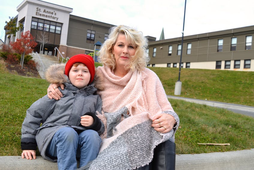 Yvonne MacKenzie sits on the curb outside St. Anne's Elementary School in Glace Bay with her son, Devon, 5. SHARON MONTGOMERY-DUPE/CAPE BRETON POST