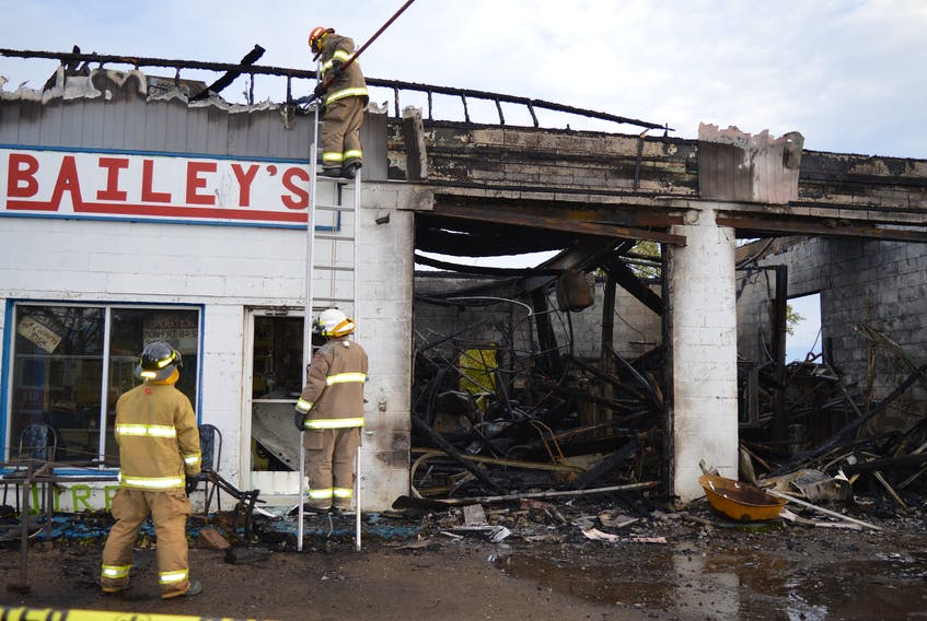 Members of the Dominion Volunteer Fire Department, from left, firefighter Edward MacNeil, Fire Chief Scott Duffney and fire captain Dave MacLeod, check out hot spots following a fire which destroyed Bailey's Service Centre on King's Road in Dominion, early Wednesday morning. Sharon Montgomery-Dupe/Cape Breton Post