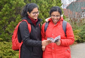 Public health students Steffi Sebastian and Siju Abraham consult the new Transit Cape Breton bus schedule while waiting for a ride at the Cape Breton University on Monday. The Glace Bay residents have been attending CBU since January and say the local transit system has been reliable and efficient.
