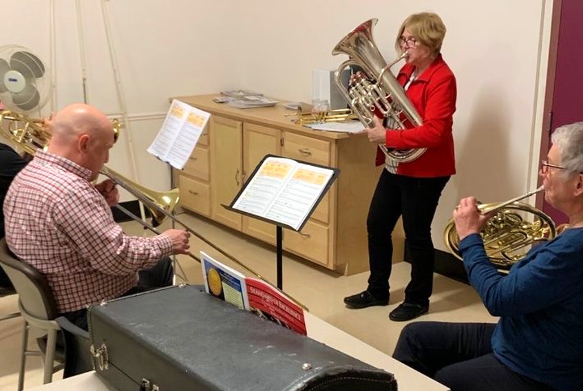Brass specialist Margaret Miles, standing, instructs from left to right, Fred Tiley on trumpet, Glenn Turner on trombone and Elizabeth Buffett on French horn during a Music For Life session.