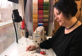 Deana Lloy, of Sydney, a kiltmaker, tartan designer and owner of Red Label Kilts, looks over the colours used to create the Absolute Darkness tartan she designed. Lloy said to kick off the sale of Absolute Darkness tartan, Red Label Kilts is giving back by donating the first 10 kilts as a numbered series in a Kilts for Coal campaign.