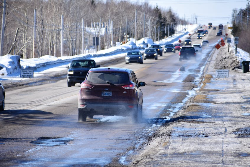 Cars drive along Route 4 in Reserve Mines on Feb. 18, swerving away from potholes in the road, causing the traffic to look slightly askew.