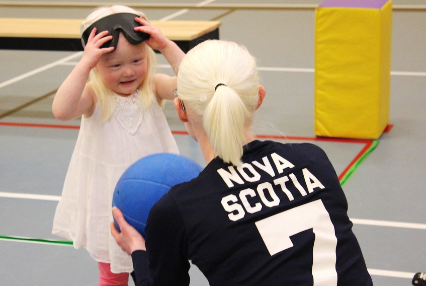 Three-year-old Lily Carmichael takes off her blindfold goggles as she speaks to women's senior provincial goalball player Jennie Bovard of Halifax.