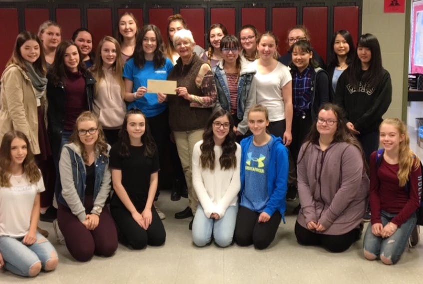Members of the Me to We group at Glace Bay High School give a cheque for $700 to the Glace Bay Food Bank through money raised through various fundraisers. In front, from the left, are Marley MacLeod, Laurelle Caume, Abby Demeyere, Brennah Messervey, Isabelle Pilling, Katie Mills, and Jordan Reid. Second row, from the left, are Alexis Howley, Chelsey McKinnon, Kelsey McLean, Kaitlyn O'Neill, Sandra McPherson, co-coordinator of the Glace Bay Food Bank Shayndel Coombes, Lara Schafer, Kokoro Nagafuji, and Mashiro Saito. Third row, from left, are Brealee Hiscock, Alyssa Ward, Leah Hynes, Faith Somerton, Mackenzie Winters, Sarah McIntyre, Madison Capstick, and Mako Hasegawa. The group also recently donated $185 to three other local food banks and $1,000 to a Me to We international community in Tanzania. (Submitted photo/Glace Bay High School)