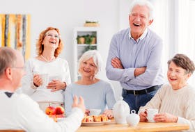 Group of happy seniors laughing together at a meeting in this stock photo.