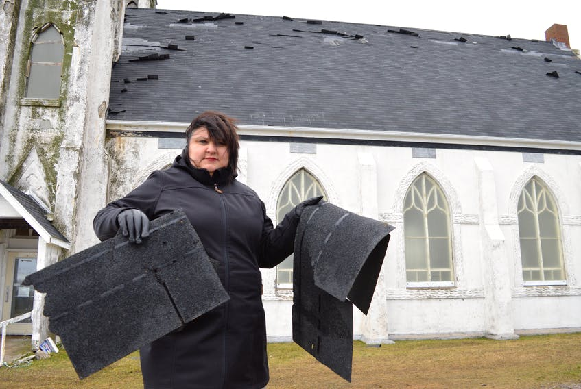 Melanie Sampson, chair of the Stone Church Restoration Society, holds up some of the pieces of shingle found on the ground at the former St. Alphonsus church in Victoria Mines after the new roof was damaged during a wind storm on Thursday. Sharon Montgomery-Dupe/Cape Breton Post