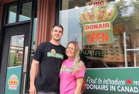 Colin Abbass and his partner Kayla Burke, both of Sydney, stand outside the King of Donair franchise they have opened on Whyte Avenue in Edmonton, Alta. It's the first permanent foray for the Halifax-based donair and pizza chain into Western Canada.