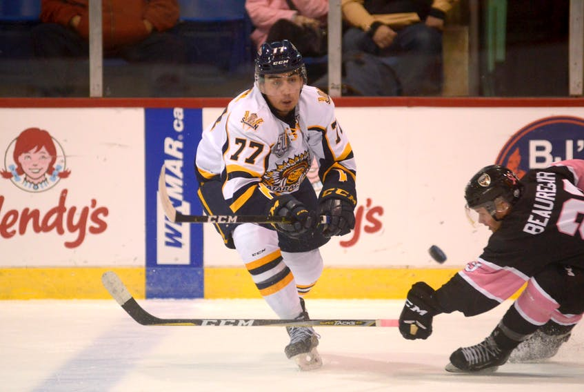 Leon Denny of the Shawinigan Cataractes, left, attempts to make a pass during a Quebec Major Junior Hockey League game against the Charlottetown Islanders last season. The Eskasoni defenceman will return to Cape Breton Thursday when the Cataractes play the Cape Breton Eagles at Centre 200 in Sydney.