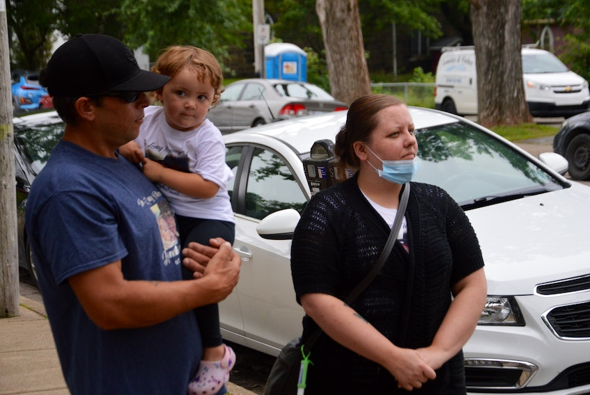 Nathan Joneil Hanna's stepfather, Steven Penney, left, Joneil's two-year-old daughter, Harper, and his mother, Jen, wait to speak with reporters Wednesday outside the Sydney Justice Centre. The family offered their reaction to the withdrawal of an obstruction charge filed against a Bras d'Or man in connection with Joneil's death in 2018.