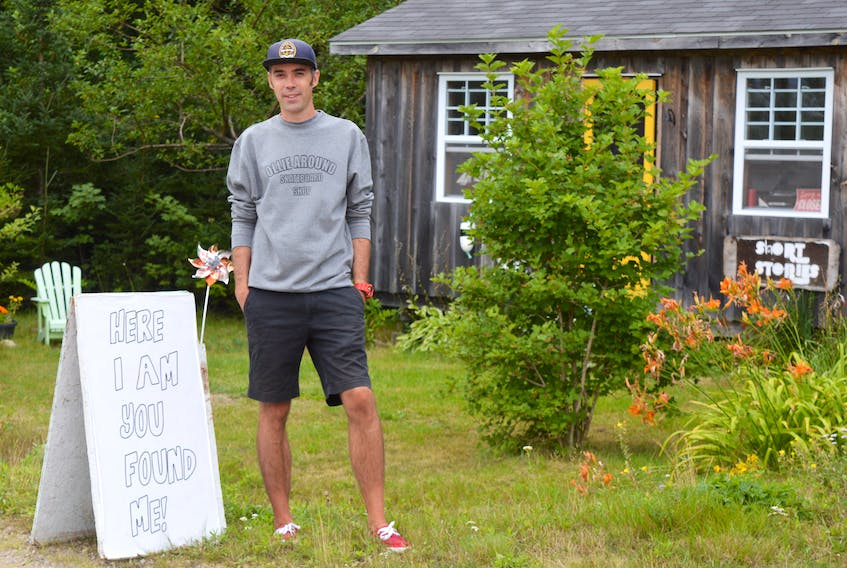 Leebly Brown, photographer and owner of Short Stories gallery located in River Bennet, stands by a sign at the edge of the road. Because the Englishtown ferry has been down all summer, Brown estimates there was a 90 per cent drop in the number of people who came to his gallery this year.