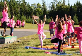Donna Lee Parker, music teacher at Riverside Elementary School, guides students through a tree pose during a short yoga practice during Pink Shirt Day activities at the school Thursday.