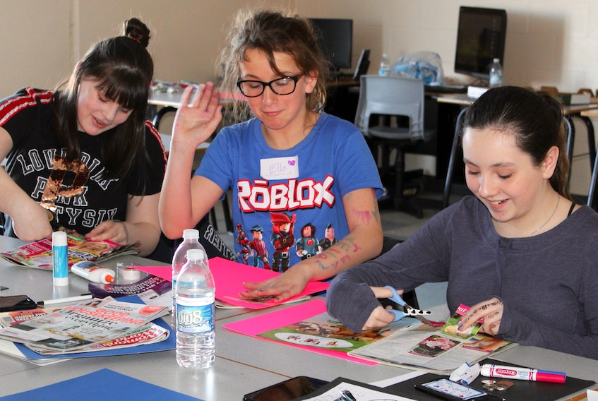 From left, Brynn White, Ella Penney and Vienna Matheson work on collages during a one-day workshop on self-esteem at Oceanview Education Centre in Glace Bay during March break.