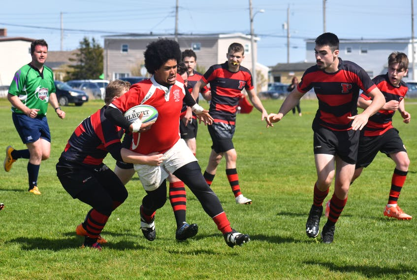 In this file photo, Braidan Sullivan, centre, of the Riverview Rugrats, gets tackled by a player from the Glace Bay Panthers at Hub Field in Glace Bay last June. Riverview will not participate in the boys' division of the Cape Breton High School Rugby League this season.