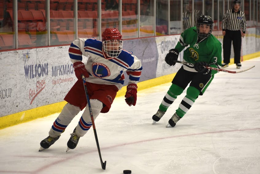 Colby McCarron of the Cape Breton County Islanders, left, carries the puck during a Nova Scotia Midget 'AA' Provincial Championship game against the Chebucto Atlantics on April 5 at the Membertou Sport and Wellness Centre. McCarron was named the Cape Breton Hockey League rookie of the year for the midget 'AA' division.