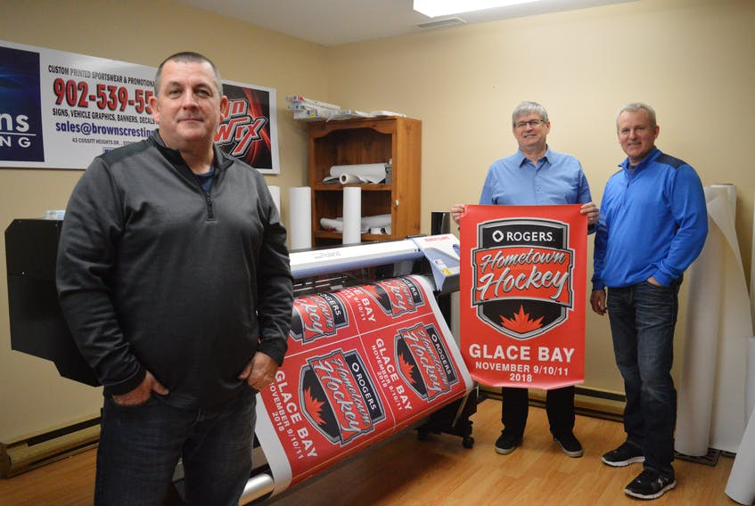 Glace Bay is gearing up for the Rogers Hometown Hockey festival this weekend by painting the town red with decorations and banners like these see-through vinyl window stickers being printed off at Brown's Cresting in Sydney. Organizers are also printing off a 40-foot banner to be put across Reserve Street and smaller banners, like the one David MacKeigan (centre) is holding. With MacKeigan, from left, are Shawn Brown and Dwight Brown, owners of Brown's Cresting.
