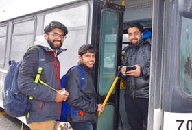 Alen Mathew Ninan, Athul Krishna and Vineeth Kumar are all smiles as they board a municipal transit bus at the Cape Breton University bus loop on Monday. The trio of petroleum engineering students from Karela, India, were not only happy to get out of the freezing cold, they were also pleased to learn that the province is spending $250,000 to help the Cape Breton Regional Municipality purchase three additional transit buses.