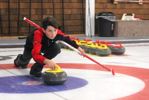 Evan Penney prepares to release a rock during a session of the Alpha/Junior curling program on Monday, Oct. 29, at the Sydney Curling Club.