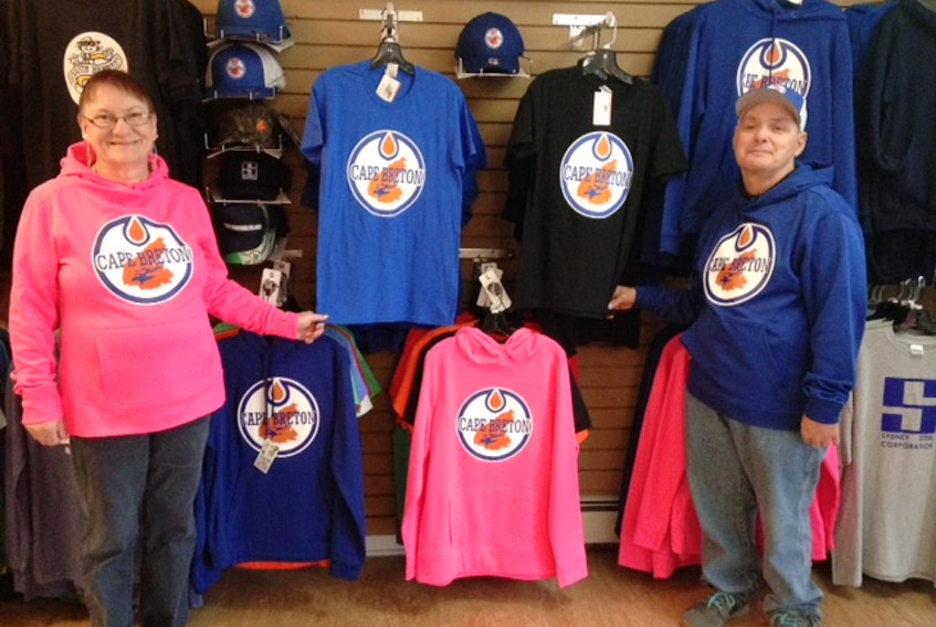Breton Ability Centre clients and Best of Cape Breton Gift Shop employees Shirley MacLean and Glen Hannon proudly display a range of Cape Breton Oilers merchandise now available at the downtown Sydney store. The shop is a social enterprise of the centre and all profits are put back into providing quality services and supports to people of varying disabilities.