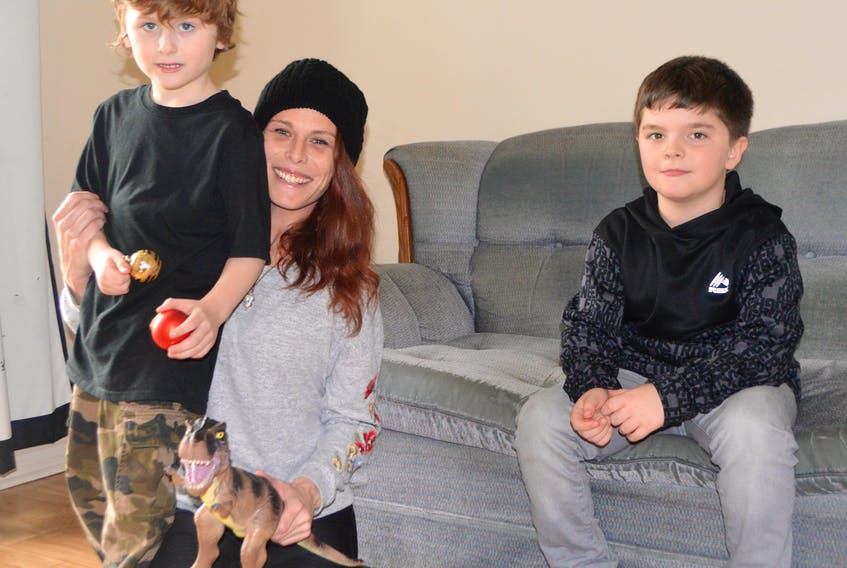 Holly Browner, 35, of Sydney relaxes with two of her three sons, including Isaac, 5, left, and Cody, 7. Browner said Isaac is severely autistic and has been on a list for life-changing assistance with the Early Intensive Behavioural Intervention program, but if he doesn't get into the program soon, he will not be eligible. Browner said her autistic son, Jake, now 10, went through the program when he was three to four years old and it changed his life.