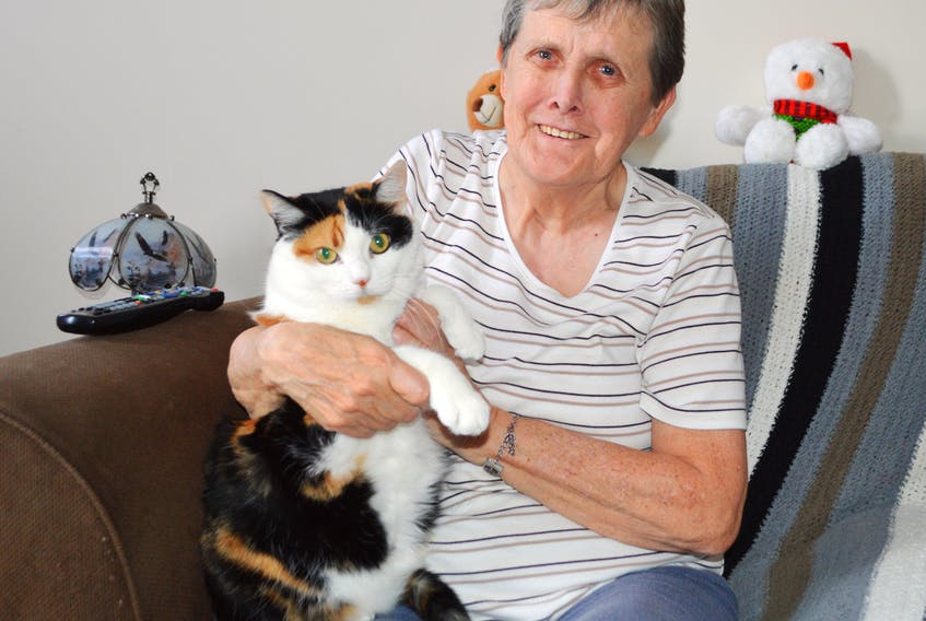 Judy James of Sydney cuddles her beloved cat Jenny in her home on Alexandra Street in Sydney. James said her company usually consists of homecare and VON, and she spends Christmas alone.