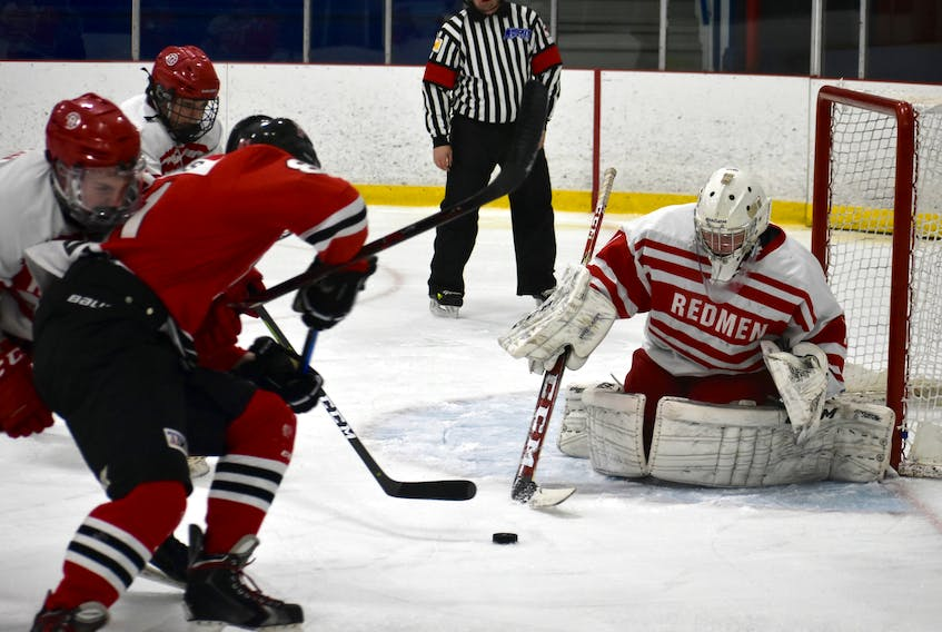 """In this file photo, Michael MacMullen of the Riverview Redmen, right, prepares to poke-check the puck during Cape Breton High School Hockey League action earlier this year at the County Recreation Centre in Coxheath. Riverview will be removing the name """"Redmen"""" from its hockey program as the school prepares to re-brand its sports team names."""