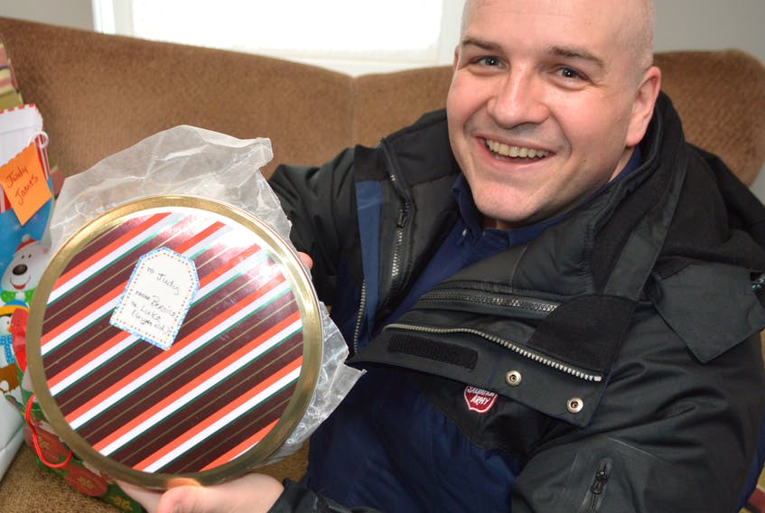 Major Corey Vincent of the Salvation Army in Sydney holds cookies and some Christmas gifts that were dropped off for Judy James, a Sydney senior spending Christmas alone. Vincent said after a story in the Cape Breton Post featured James and another lonely senior in North Sydney, the response from people wanting to help has been amazing.