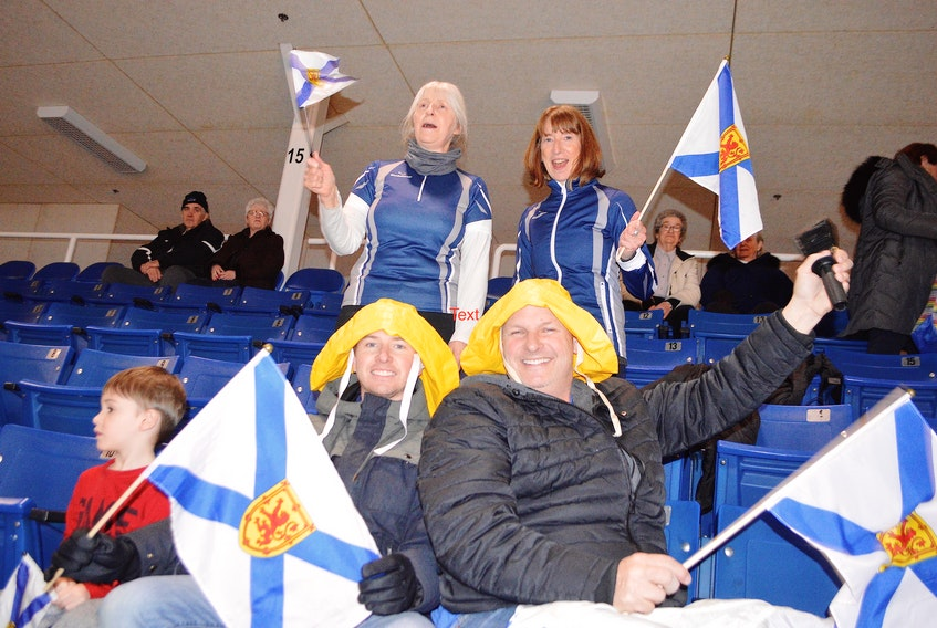 Family members of Nova Scotia skip Jill Brothers – Sou'Westers and all – were cheering her team on during the Scotties Tournament of Hearts at Centre 200 in Sydney Tuesday including, in front from the left, her son Casey, 4, husband Paul Brothers, step father Gifford Fralac, and in back from the left, mother-in-law Susan Brothers and friend Elspeth Carmody, mother of Nova Scotia curler Erin Carmody. Jill has a huge family following at all tournaments and bonspiels.