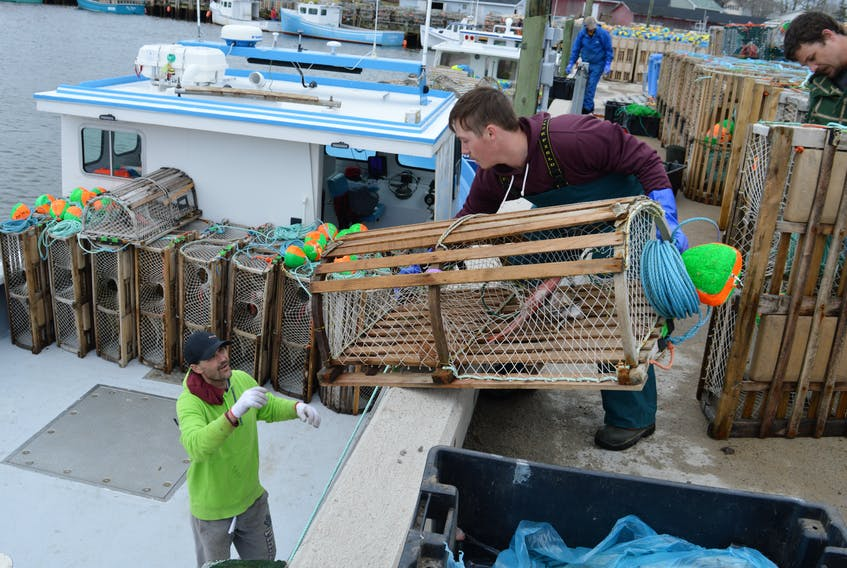 From the left, Kevin Ogley, receives a trap from Dylon Turnbull and Kevin Ogley on board the Mark and Brett. The season continues until July 15 in lobster fishing area 27.