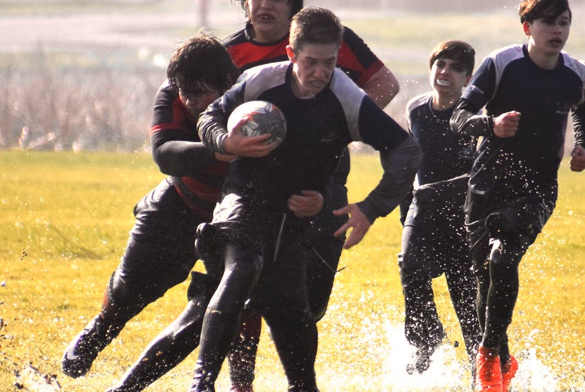 Dawson MacNeil of the Sydney Academy Wildcats runs the ball as he's tackled by Jonathan Roach of the Glace Bay Panthers during the Highland region boy's rugby championship game Wednesday at Hub Field in Glace Bay. The Panthers won the game 54-0 and will play in the provincial championship later this month.