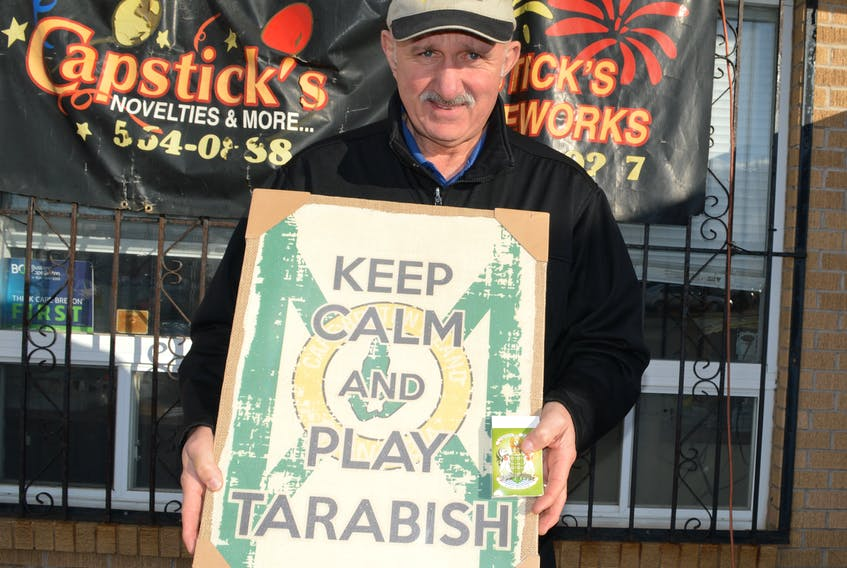 Angus Capstick, owner of Capstick's Novelties and More, holds some of the tarabish-related items he sells at his Liberty Street wholesale store.