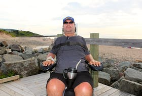 Callum MacQuarrie sits in his motorized wheelchair on the boardwalk at Inverness beach on Tuesday. In the background is the breakwater where he broke his neck diving into the shallow water below 23 years ago. MacQuarrie, who is co-chair of the Inverness County accessibility committee, helped lead the charge to make Inverness beach the most accessible beach in Atlantic Canada.
