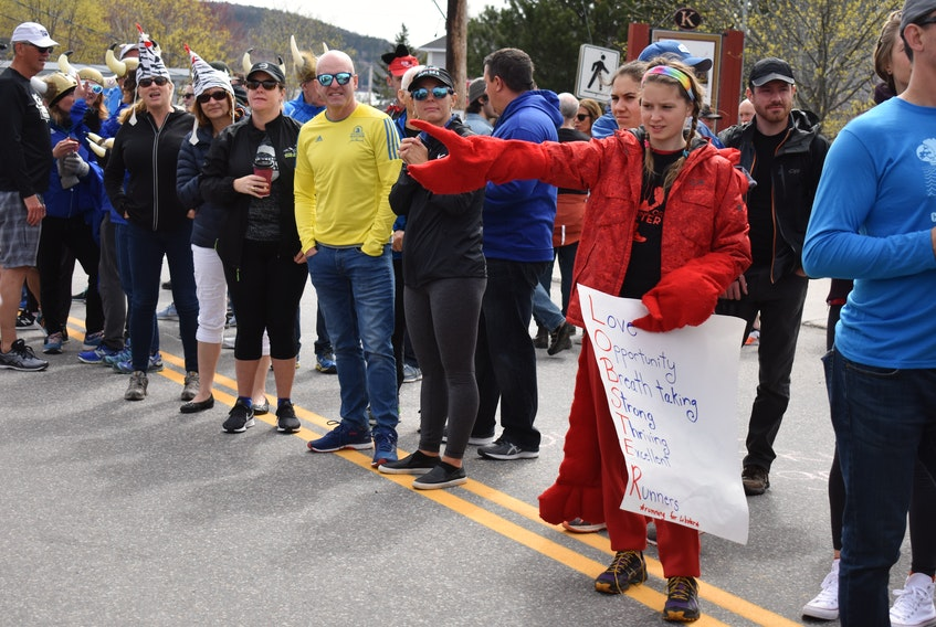 "Dressed as a lobster, her team's mascot, Jillian Thomas stretches out her hand in hopes a runner will hit her ""claw"" as they make it to the finish line. The 12-year-old has been coming with her mother to cheer on their team since she was four."