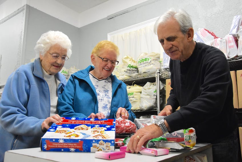 Constance Nickerson, left, Jean Landry and Lawrence Shebib look through different Christmas goodies in preparation for the Christmas Cheer dinner program. So far, the program has more than 200 people registered.