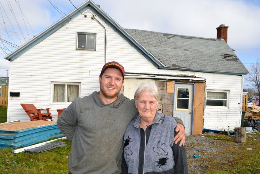 Jeremy Locke, owner of Locke's Roofing and Construction in Bridgeport, stands with Jeanette MacDonald outside her home in Glace Bay. Locke, seeing her roof was in deplorable shape, simply knocked on her door offering to replace it for free back in the spring, but it took a little trick months later to get her to accept. MacDonald said she's extremely grateful to Locke, as her roof has been bad for a couple years, but this past year took a beating with storms and there are numerous leaks in the house.
