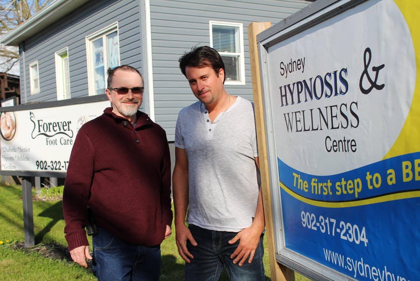 Glenn MacDonald, left, and Carmen Giorno stand outside their Sydney Hypnosis and Wellness Centre located at 250 Welton St. in Sydney. The two are trained hypnotherapists who have been helping clients for about a year and a half.