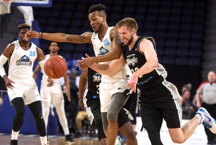 Halifax Hurricanes' Joel Kindred, left, and Moncton Magic's Wayne McCullough chase down a loose ball during the first half of Friday night's NBL Canada playoff game at the Scotiabank Centre.